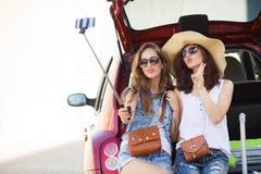 Twee meisjes -meisje-selfie in de boomstam van een auto Royalty-vrije Stock Foto's