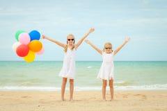 Twee meisjes met ballons die zich op het strand bij de dag bevinden royalty-vrije stock foto