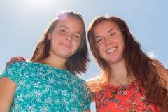 Twee Meisjes met Blauwe Hemel en Zonlicht op de Achtergrond Stock Afbeelding