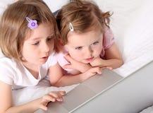 Twee meisjes met computer stock afbeeldingen