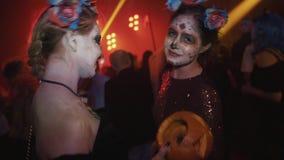 Twee meisjes met de verfdans van het santa muerte gezicht bij de partij van Halloween van de nachtclub stock video