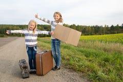 Twee meisjes met koffer die zich over weg bevinden Stock Afbeelding