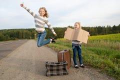 Twee meisjes met koffer die zich over weg bevinden Royalty-vrije Stock Foto