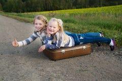 Twee meisjes met koffer die zich over weg bevinden Royalty-vrije Stock Foto's