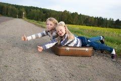 Twee meisjes met koffer die zich over weg bevinden Stock Foto's