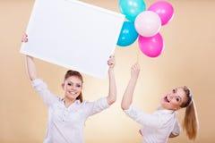Twee meisjes met lege raad en ballons Stock Foto's