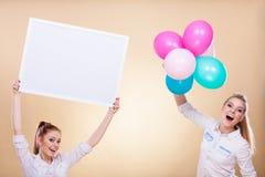 Twee meisjes met lege raad en ballons Stock Foto