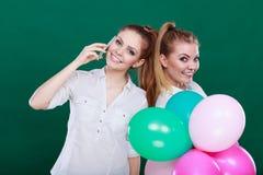 Twee meisjes met mobiele telefoon en ballons Stock Fotografie