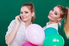 Twee meisjes met mobiele telefoon en ballons Stock Afbeelding