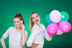 Twee meisjes met mobiele telefoon en ballons Stock Foto