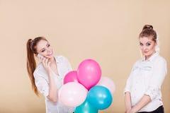 Twee meisjes met mobiele telefoon en ballons Stock Afbeeldingen