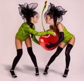 Twee meisjes met reusachtige kers stock fotografie