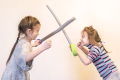 Twee meisjes met stuk speelgoed de ridders van het zwaardenspel Children& x27; s emoties royalty-vrije stock fotografie