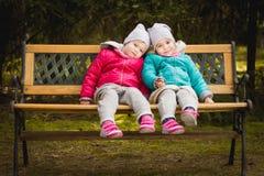 Twee meisjes op een bank in het hout Stock Afbeeldingen