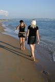 Twee meisjes op een strand gaan veraflegen Stock Foto's