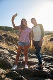 Twee meisjes op rots het stellen stock afbeeldingen