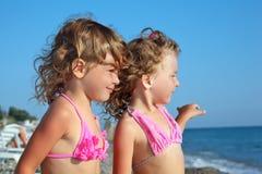 Twee meisjes op strand, dat veraflegen kijkt Stock Afbeeldingen