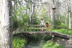 Twee meisjes over een houten brug over een stroom Stock Afbeelding
