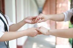 Twee meisjes overhandigen hand in hand dicht op tribune voor vriendschap Stock Foto's