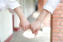 Twee meisjes overhandigen hand in hand dicht op tribune voor vriendschap Stock Foto