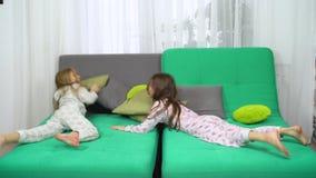 Twee meisjes in pyjama'ssprong binnen op bank en de strijd van het beginhoofdkussen stock video