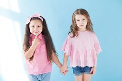 Twee meisjes in roze kledingsmeisjes houden handen royalty-vrije stock foto