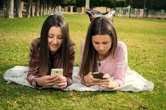 Twee meisjes schrijven in mobiele telefoons stock afbeeldingen