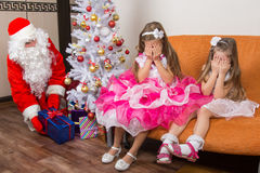 Twee meisjes sloten ogen met zijn handen tot gezette Santa Claus onder Kerstboom voorstelt Royalty-vrije Stock Afbeelding