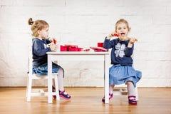 Twee meisjes spelen bij de lijst Stock Foto's