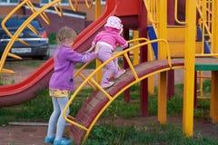 Twee meisjes spelen op de speelplaats Stock Foto