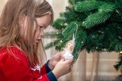 Twee meisjes stellen en voor de gek houden rond de Kerstboom stock afbeelding