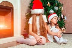 Twee meisjes stellen en voor de gek houden rond de Nieuwjaarboom stock afbeeldingen