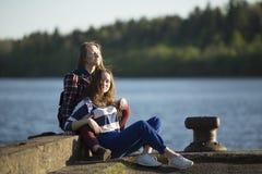 Twee meisjes van de vriendentiener brengen samen tijd bij de pijler door Stock Foto's