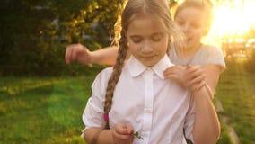 Twee meisjes van het schoolmeisje omhelzen in stralen van de het plaatsen zon Terug naar school, gelukkige kinderjaren stock footage