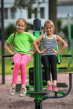 Twee meisjes voeren in openlucht gymnastiek- oefeningen uit Sport stock afbeelding