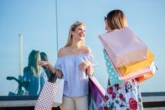Twee meisjes voor het winkelvenster, dragende het winkelen zakken Bezinningen in Glas stock fotografie