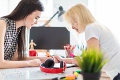 Twee meisjes werken in het bureau stock foto's