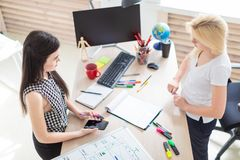 Twee meisjes werken in het bureau Meisje die een telefoon houden stock foto's