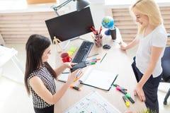 Twee meisjes werken in het bureau Meisje die een telefoon houden royalty-vrije stock afbeeldingen