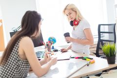 Twee meisjes werken in het bureau Het meisje houdt een model van een mens stock foto