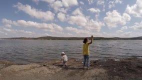 Twee meisjes werpen stenen in het water Langzame Motie stock footage