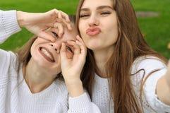 Twee meisjes worden voor de gek gehouden door grimassen te tonen, terwijl zij maken royalty-vrije stock foto's