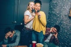 Twee meisjes zingen een zeer luid lied Hun vriend trekt ` t als het aan omdat de jonge vrouwen ` t zingen zeer goed bij allen aan stock afbeeldingen