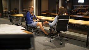 Twee meisjes zitten in commercieel centrum, roddelen en bespreken bedrijfsideeën stock video