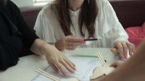 Twee meisjes zitten in een koffie, bespreken bedrijfsideeën en brengen lunchnoedels aan hen stock video