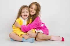 Twee meisjes zitten in robes stock foto's