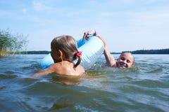 Twee meisjes zwemmen in een meer Stock Foto's