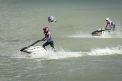 Twee meisjesatleten slepen dapper langs de overzeese golven op aquabike mee royalty-vrije stock afbeelding