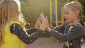 Twee meisjeskleuters rond en het spelen pasteitje-cake die voor de gek houden stock footage