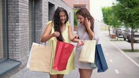 Twee meisjesmeisjes in kleding bespreken het winkelen na het winkelen Langzame Motie stock footage